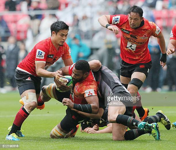 This picture taken on February 13 2016 shows Japan's Sunwolves player Andrew Durutalo being tackled during a charity rugby match in Toyota Aichi...