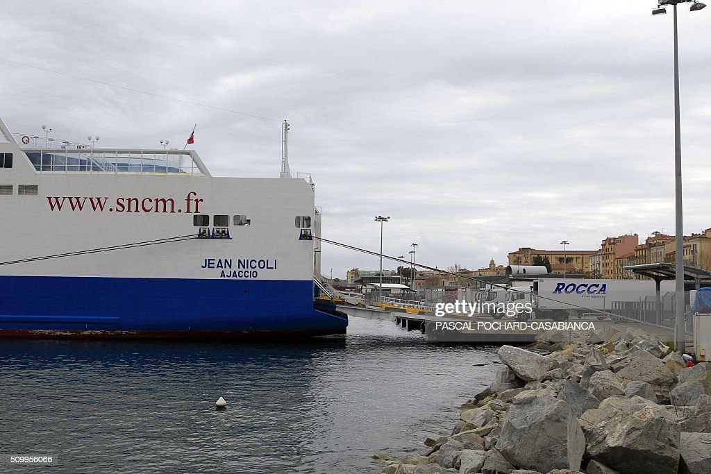 This picture taken on February 13, 2016 shows the former SNCM ferry boat 'Jean Nicoli' docked at Ajaccio's port, with trucks parked in front of its boarding ramp to avoid freight loading, on the French Mediterranean island of Corsica. / AFP / PASCAL POCHARD CASABIANCA