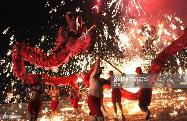 This picture taken on February 14 2014 shows Chinese villagers perform a dragon dance to celebrate the lantern festival in Yongchuan Chongqing...