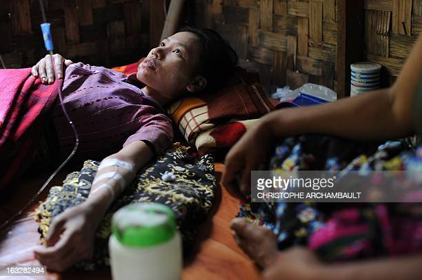 This picture taken on February 15 2013 shows an HIV patient lying on a mat as she is administered medicine through an intravenous infusion at a...