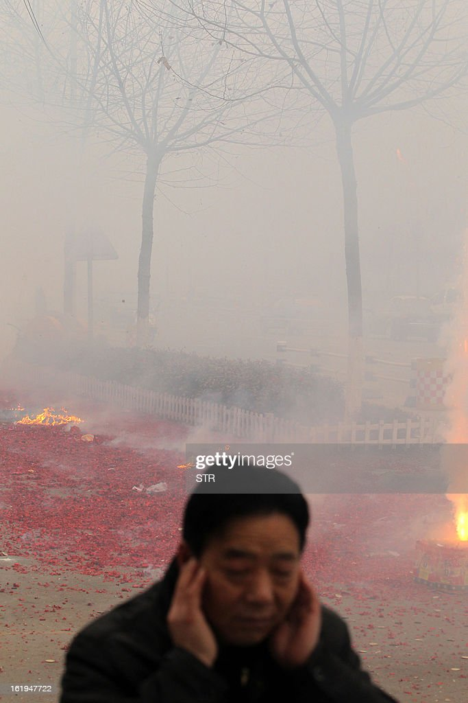 This picture taken on February 16, 2013 shows a man covering his ears as firecrackers explode behind him during celebrations of the Chinese lunar new Year of the Snake in Xuchang, central China's Henan province. The season is a peak period for fireworks producers, as Chinese traditionally buy the explosives to celebrate the festival, which fell on February 10 this year. CHINA OUT AFP PHOTO
