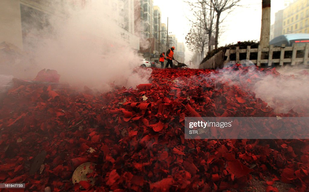 This picture taken on February 16, 2013 shows city cleaners (C) clearing used fireworks as firecrackers explode during celebrations of the Chinese lunar new Year of the Snake in Xuchang, central China's Henan province. The season is a peak period for fireworks producers, as Chinese traditionally buy the explosives to celebrate the festival, which fell on February 10 this year. CHINA OUT AFP PHOTO
