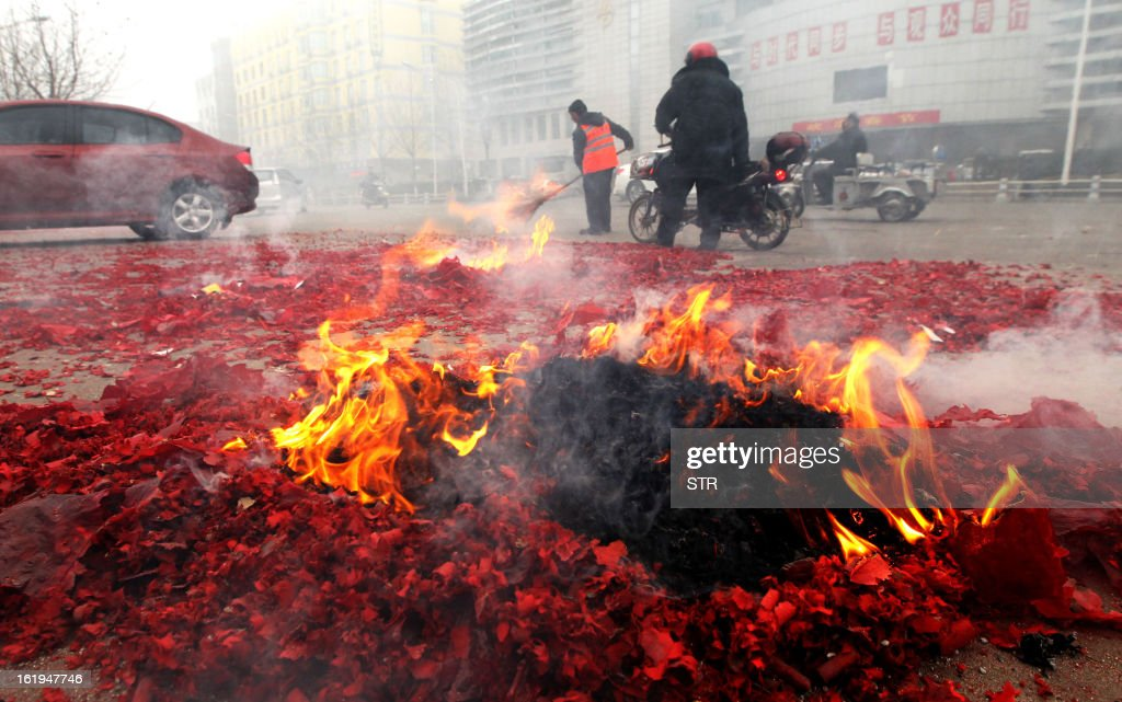 This picture taken on February 16, 2013 shows city cleaners clearing used fireworks after a firework display to celebrate the Chinese lunar new Year of the Snake in Xuchang, central China's Henan province. The season is a peak period for fireworks producers, as Chinese traditionally buy the explosives to celebrate the festival, which fell on February 10 this year. CHINA