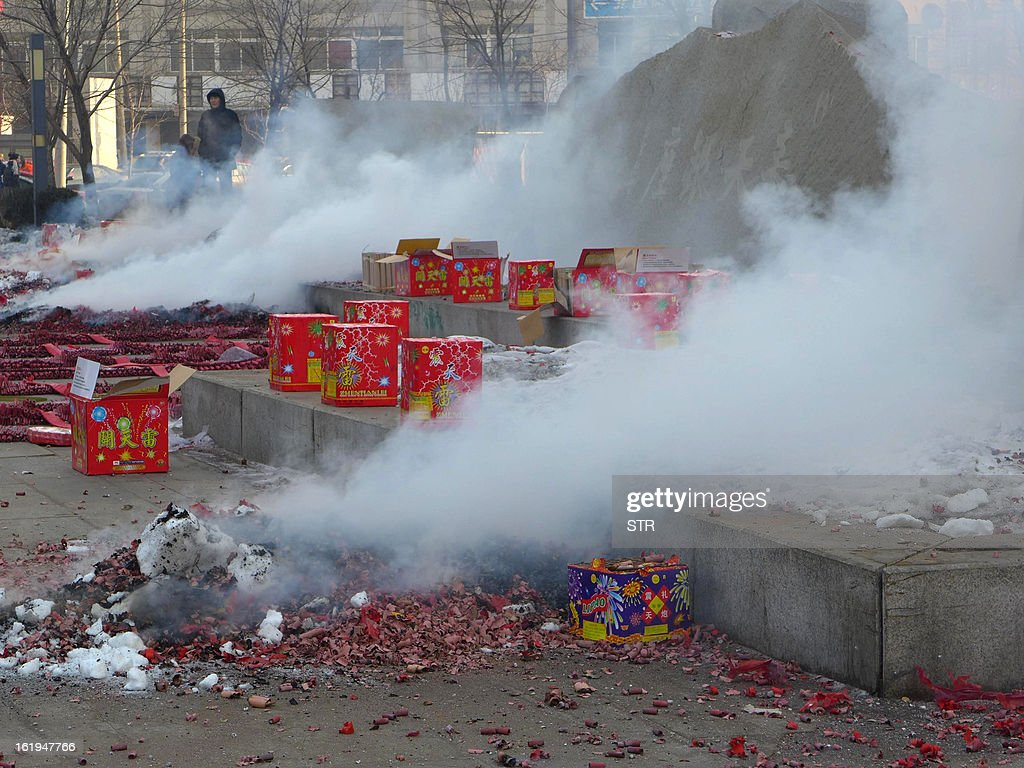 This picture taken on February 16, 2013 shows firecrackers giving off smoke during a firework display to celebrate the Chinese lunar new Year of the Snake in Shenyang, northeast China's Liaoning province. The season is a peak period for fireworks producers, as Chinese traditionally buy the explosives to celebrate the festival, which fell on February 10 this year. CHINA