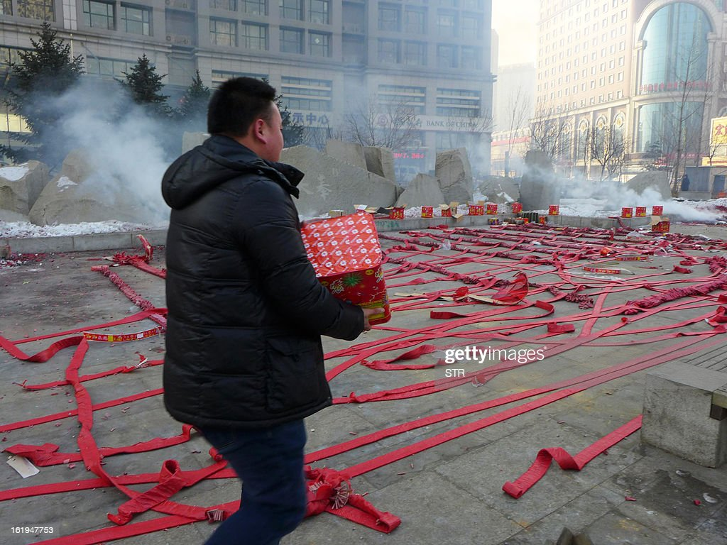 This picture taken on February 16, 2013 shows people preparing a firework display to celebrate the Chinese lunar Year of the Snake in Shenyang, northeast China's Liaoning province. The season is a peak period for fireworks producers, as Chinese traditionally buy the explosives to celebrate the festival, which fell on February 10 this year. CHINA OUT AFP PHOTO