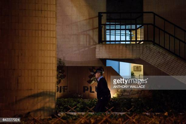 This picture taken on February 16 2017 shows a policeman patrolling the grounds of a residential building where Kim JongNam halfbrother of a North...