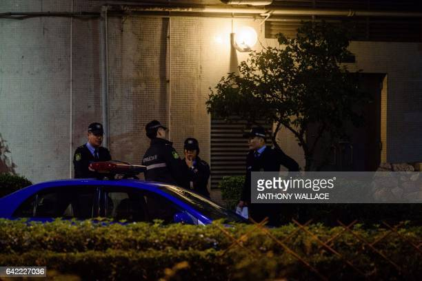 This picture taken on February 16 2017 shows police standing outside the grounds of a residential building where Kim JongNam halfbrother of a North...