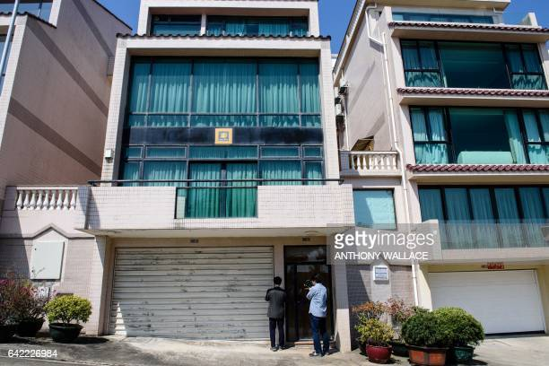 This picture taken on February 16 2017 shows South Korean journalists standing outside an oceanfront villa one of the properties where Kim JongNam...