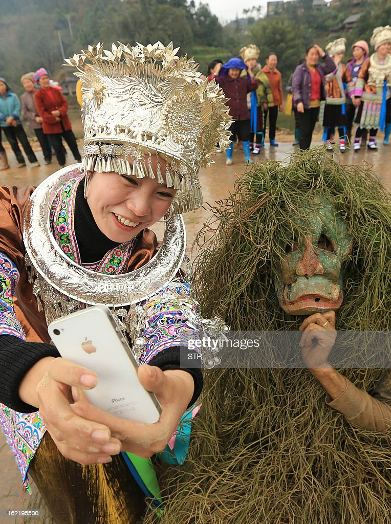 This picture taken on February 18, 2013 shows a girl taking photo of her and a 'Mang Hao' as people celebrate the traditional Miao Minority 'Mang Hao' ('Mang' means 'mask' and 'Hao' means 'god') festival in Rongan, southwest China's Guangxi province. During the festival, young people with good merits dress themselves as 'Mang Hao' and pat others in order to give out good wishes. CHINA