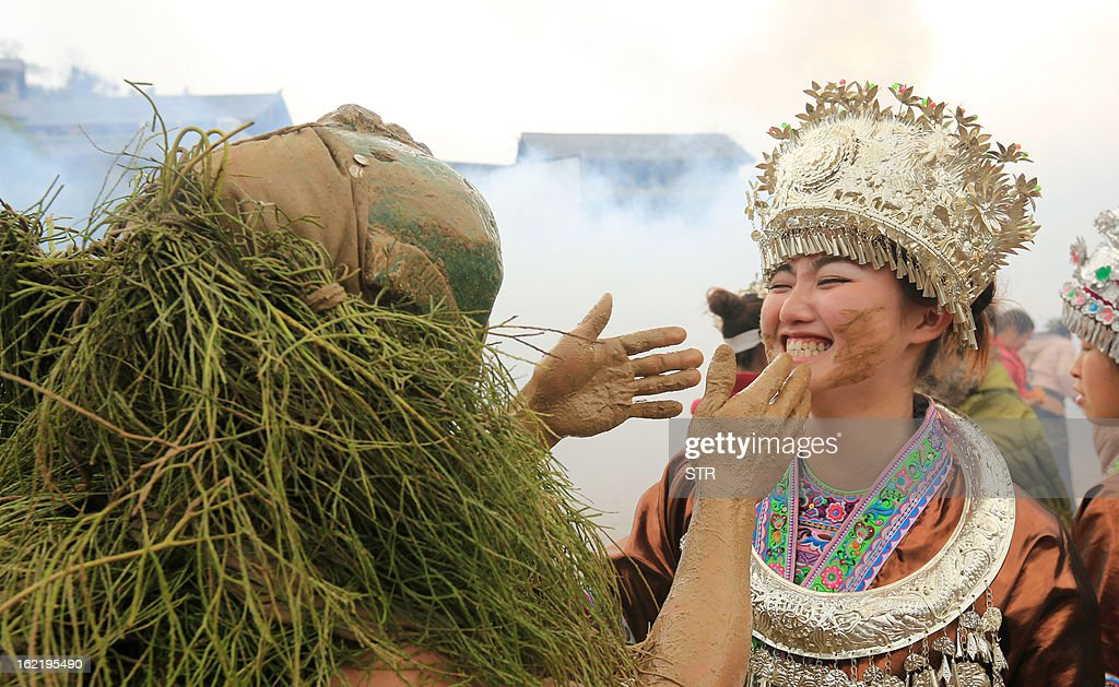 This picture taken on February 18, 2013 shows a 'Mang Hao' touching a girl's face as part of celebrations of the traditional Miao Minority 'Mang Hao' ('Mang' means 'mask' and 'Hao' means 'god') festival in Rongan, southwest China's Guangxi province. During the festival, young people with good merits dress themselves as 'Mang Hao' and pat others in order to give out good wishes. CHINA