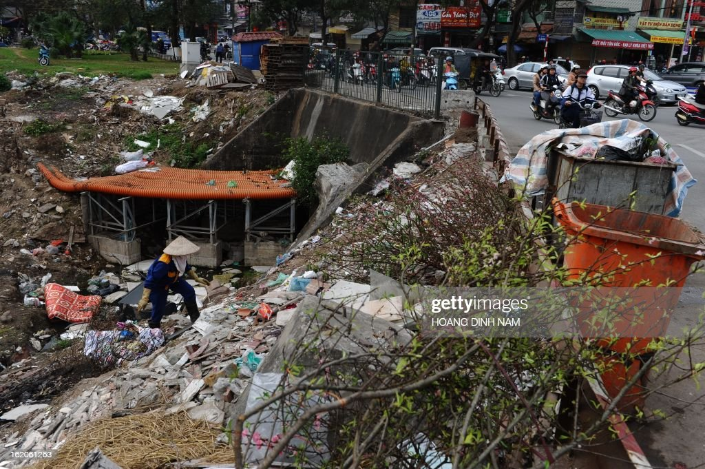 This picture taken on February 18, 2013 shows a municipal environmental worker (L) collecting garbage and recyclable items along the heavily polluted canal of To Lich as commuters drive along an adjoining road in Hanoi. AFP PHOTO/HOANG DINH Nam