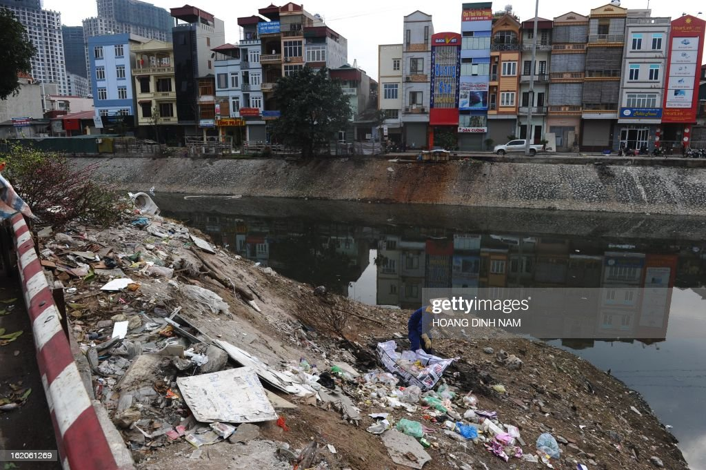 This picture taken on February 18, 2013 shows a municipal environmental worker collecting garbage and recyclable items along the heavily polluted canal of To Lich in Hanoi. AFP PHOTO/HOANG DINH Nam