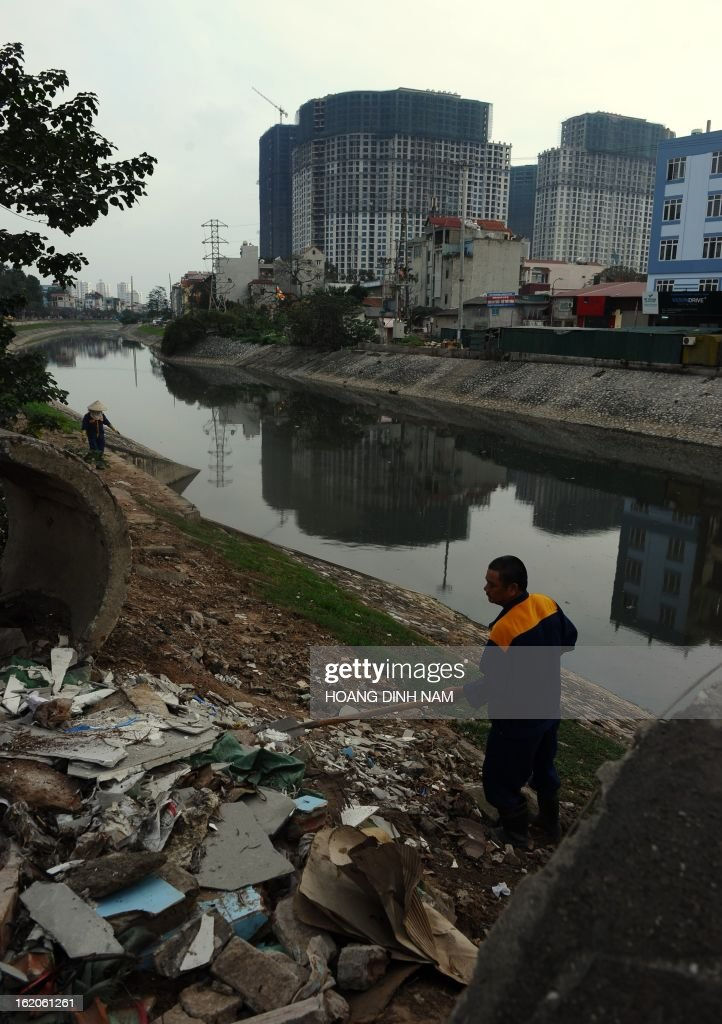 This picture taken on February 18, 2013 shows municipal environmental workers collecting garbage and recyclable items along the heavily polluted canal of To Lich in Hanoi. AFP PHOTO/HOANG DINH Nam