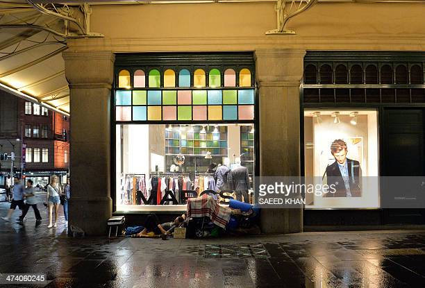 This picture taken on February 19 2014 show a homeless man sleeping outside a shop during a wet night in down town Sydney G20 host Australia said on...