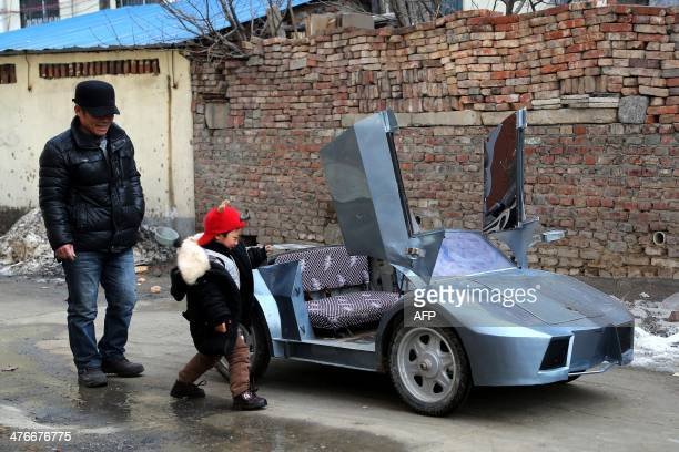 This picture taken on February 19 2014 shows Guo a farmer in his 50s stands by his selfmade scale replica of a Lamborghini with his grandson in a...