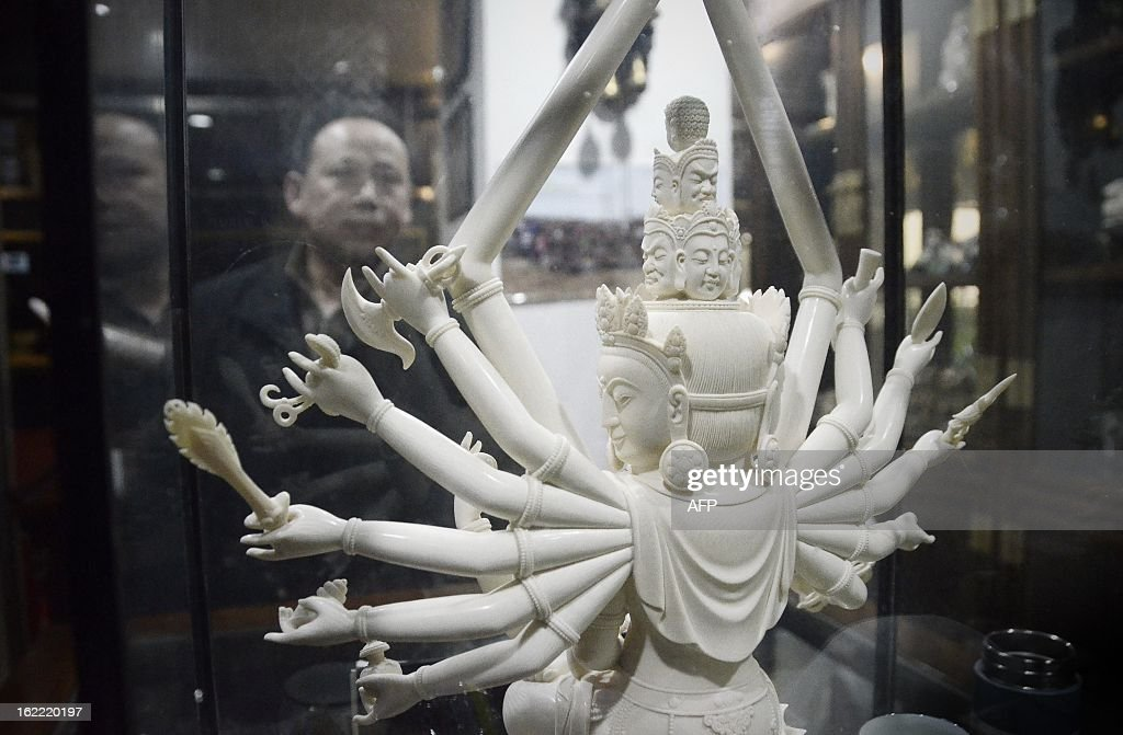 This picture taken on February 20, 2013 shows a Chinese man looking at an ivory Buddha carving at a shop in Beijing. The number of African elephants killed by poachers in 2012 will most likely be higher than the 25,000 illegally killed the previous year, the head of UN wildlife trade regulator CITES said on Februay 19. One kilogramme (about two pounds) of ivory is currently estimated to be worth around 2,000 USD on the Asian black market. AFP PHOTO / WANG ZHAO