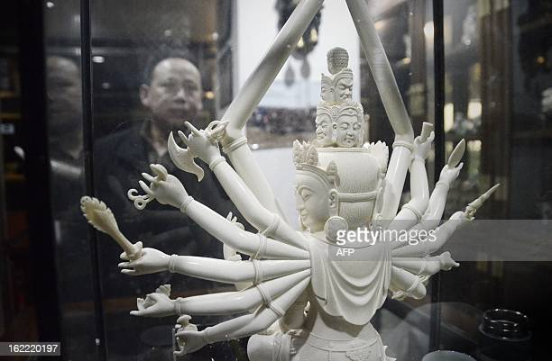 This picture taken on February 20 2013 shows a Chinese man looking at an ivory Buddha carving at a shop in Beijing The number of African elephants...