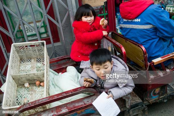 This picture taken on February 20 2017 shows children playing on the back of a tricycle in a hutong in Beijing With space scarce in the city of 215...