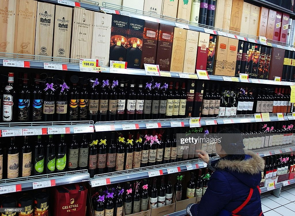 This picture taken on February 21, 2014 shows a customer choosing wine in a supermarket in Yichang, central China's Hubei province. The Chinese and European wine industries have agreed a deal that will see Beijing end an anti-dumping inquiry into imports from the European Union, China's commerce ministry said on March 21. CHINA