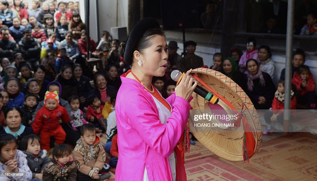 This picture taken on February 22, 2013 shows a folk singer performing as villagers watch at a communal house of a village on the outskirts of Hanoi. Numerous spring festivities are being held during weeks following the Lunar New Year or Tet celebrations throughout villages in northern Vietnam. AFP PHOTO/HOANG DINH Nam