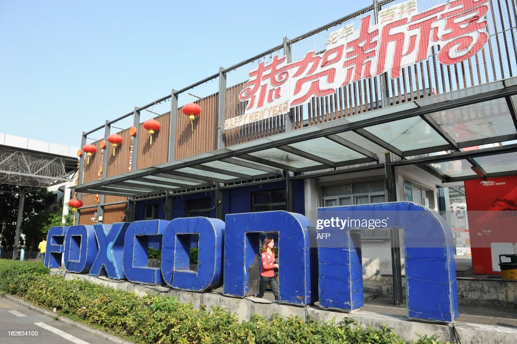This picture taken on February 22, 2013 shows a young woman walking past a Foxconn recruitment point in Shenzhen, south China's Guangdong province. Taiwan technology giant Foxconn has slowed new hiring at its vast China factories, it said on February 21, but denied the move was linked to weak demand for Apple's iPhone 5, which it produces. CHINA