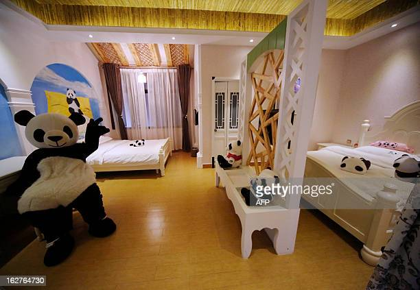 This picture taken on February 22 2013 shows an employee wearing a panda suit introducing the rooms in a pandathemed hotel at the foot of Emei...