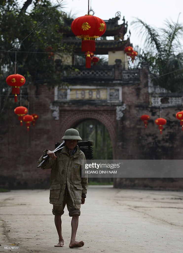 This picture taken on February 23, 2013 shows a man walking under Chinese-made red lanterns hanging in the village of Uoc Le on the outskirts of Hanoi for the Lunar New Year or, known as the Tet celebration in Vietnam. Many northern Vietnamese Red River delta localities, especially in rural areas, have been decorated with imported Chinese-made red lanterns for the celebrations. Earlier this month the local daily Tuoi Tre (Youth) reported some Chinese-made lanterns bearing the Chinese characters 'Nansha', the Chinese name of the disputed Spratley islands chain in the South China Sea in which Vietnam also stakes claims, had been seized by local Vietnamese authorities in northern Vietnam. AFP PHOTO / HOANG DINH Nam