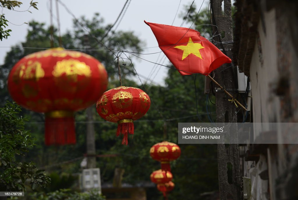 This picture taken on February 23, 2013 shows a Vietnamese flag (R) flying next to Chinese-made red lanterns hanging in the village of Uoc Le on the outskirts of Hanoi for the Lunar New Year or, known as the Tet celebration in Vietnam. Many northern Vietnamese Red River delta localities, especially in rural areas, have been decorated with imported Chinese-made red lanterns for the celebrations. Earlier this month the local daily Tuoi Tre (Youth) reported some Chinese-made lanterns bearing the Chinese characters 'Nansha', the Chinese name of the disputed Spratley islands chain in the South China Sea in which Vietnam also stakes claims, had been seized by local Vietnamese authorities in northern Vietnam. AFP PHOTO / HOANG DINH Nam