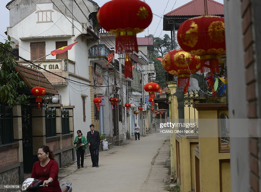 This picture taken on February 23, 2013 shows Chinese-made red lanterns hanging in the village of Uoc Le on the outskirts of Hanoi for the Lunar New Year or, known as the Tet celebration in Vietnam. Many northern Vietnamese Red River delta localities, especially in rural areas, have been decorated with imported Chinese-made red lanterns for the celebrations. Earlier this month the local daily Tuoi Tre (Youth) reported some Chinese-made lanterns bearing the Chinese characters 'Nansha', the Chinese name of the disputed Spratley islands chain in the South China Sea in which Vietnam also stakes claims, had been seized by local Vietnamese authorities in northern Vietnam. AFP PHOTO / HOANG DINH Nam