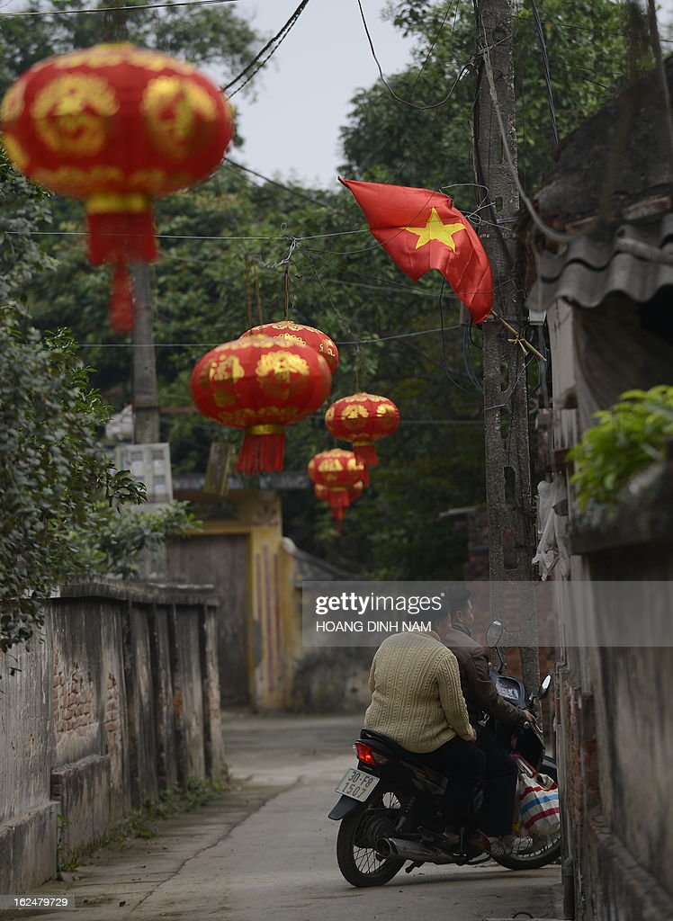 This picture taken on February 23, 2013 shows villagers riding a motorbike under Chinese-made red lanterns hanging in the village of Uoc Le on the outskirts of Hanoi for the Lunar New Year or, known as the Tet celebration in Vietnam. Many northern Vietnamese Red River delta localities, especially in rural areas, have been decorated with imported Chinese-made red lanterns for the celebrations. Earlier this month the local daily Tuoi Tre (Youth) reported some Chinese-made lanterns bearing the Chinese characters 'Nansha', the Chinese name of the disputed Spratley islands chain in the South China Sea in which Vietnam also stakes claims, had been seized by local Vietnamese authorities in northern Vietnam. AFP PHOTO / HOANG DINH Nam