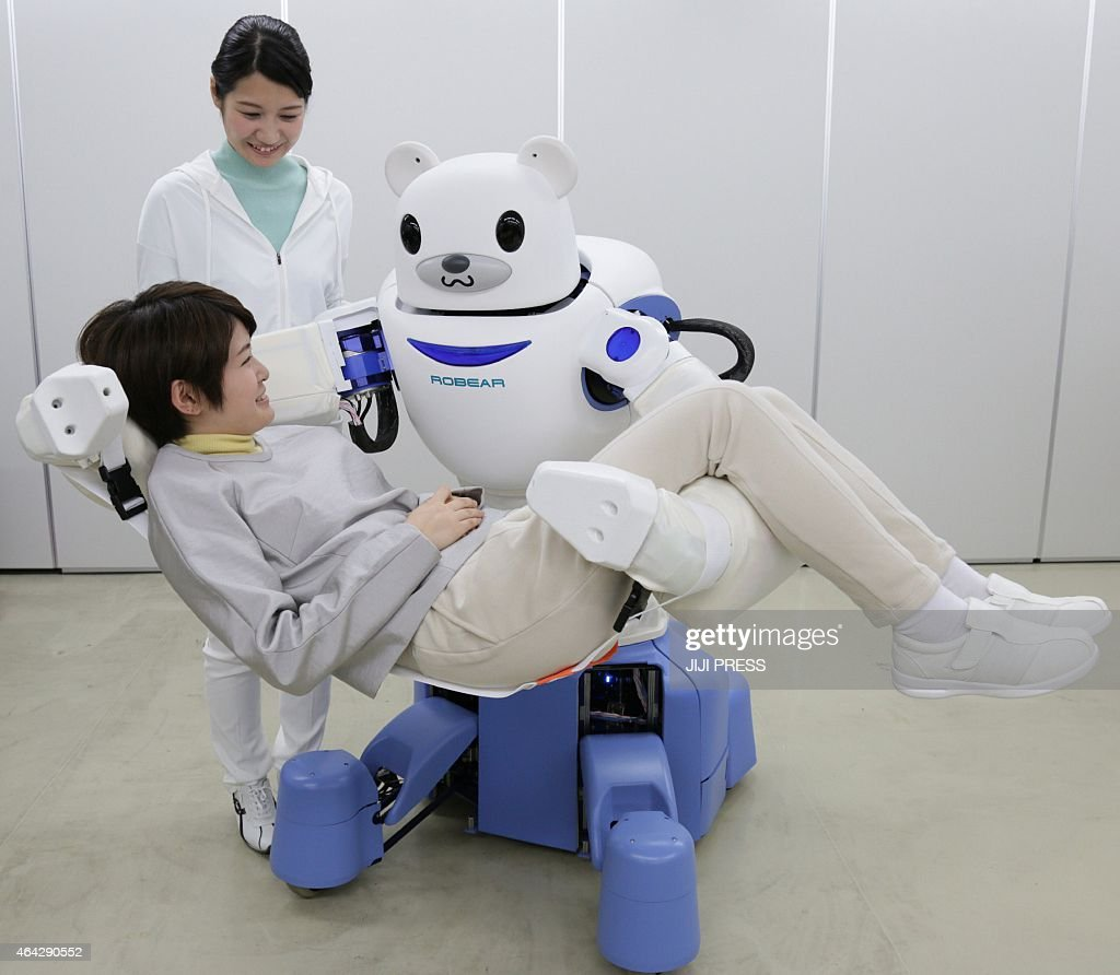 This picture taken on February 23 2015 shows a polar bear robot 'Robear' lifting a woman for a demonstration in Nagoya central Japan The 'Robear'...