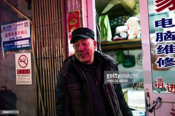 This picture taken on February 23 2017 shows Gu Chen an electrical appliance repairman standing in front of his oneroom apartment where he has slept...