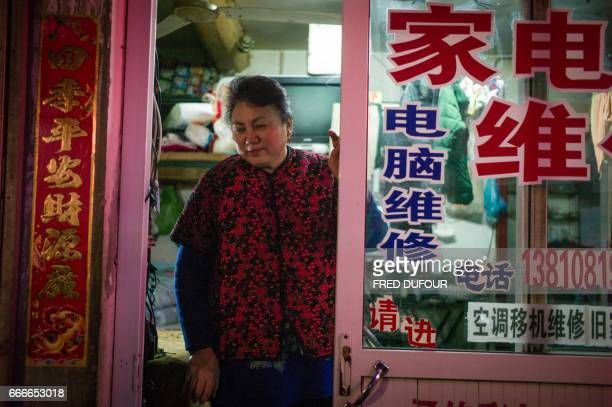 This picture taken on February 23 2017 shows the wife of Gu Chen an electrical appliance repairman stands in front of the oneroom apartment where she...