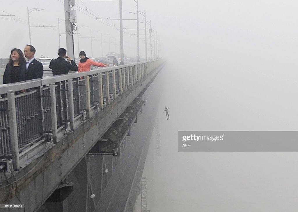 This picture taken on February 27, 2013 shows a youngster (R) jumping from Yangtze River Bridge in Wuhan, central China's Hubei province into the river following another person who committed suicide minutes before. Police said there was little chance for them to survive and one of the two was a young male that was born in May, 1993. CHINA OUT AFP PHOTO