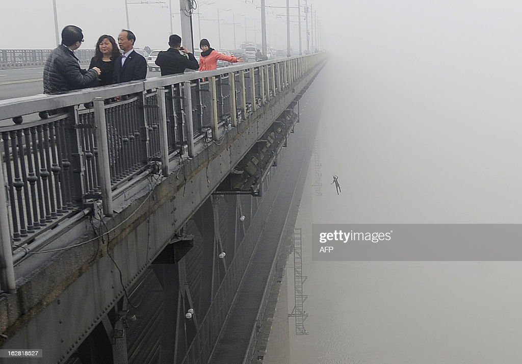 This picture taken on February 27, 2013 shows a youngster jumping from Yangtze River Bridge in Wuhan, central China's Hubei province into the river following another person who committed suicide minutes before. Police said there was little chance for them to survive and one of the two was a young male that was born in May, 1993. CHINA