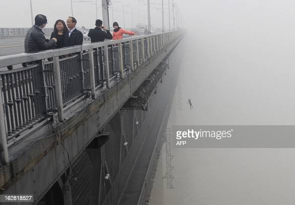 This picture taken on February 27 2013 shows a youngster jumping from Yangtze River Bridge in Wuhan central China's Hubei province into the river...