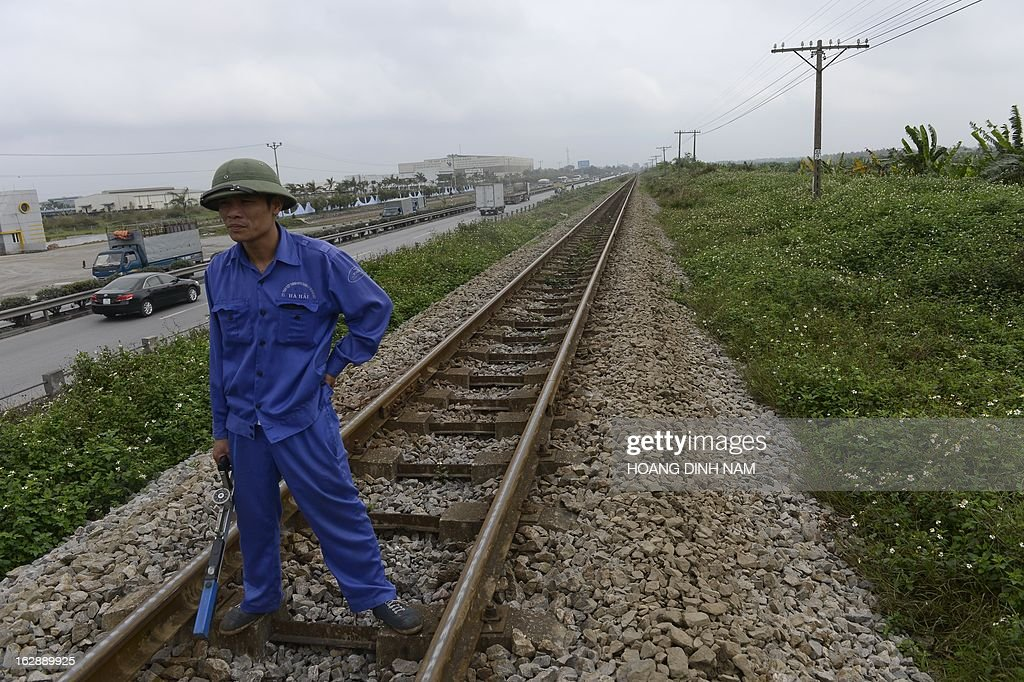 This picture taken on February 28, 2013 shows a railway maintenance service's technician inspecting a portion of a railway in northern province of Hai Duong. Vietnam's railway network, whose status is described by some official published reports as remaining the same one as hundred years ago when it was first built in French colonial time, is subjected to a national upgrading program approved by the central government. AFP PHOTO/HOANG DINH Nam