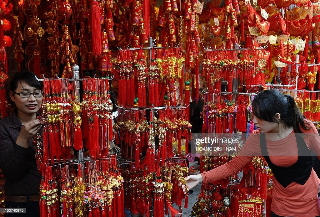 This picture taken on February 4, 2013 shows a customer browsing Chinese decorative hanging items for the lunar new year or Tet celebrations at a Tet market in downtown Hanoi. With the upcoming lunar new year celebrations, vendors and sales staff are attempting to make the last transactions before the holidays begin. AFP PHOTO/HOANG DINH Nam