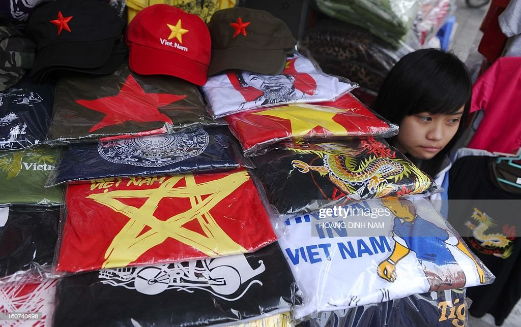 This picture taken on February 4, 2013 shows a girl sitting next to her stand of souvenir T-shirts in the ancient quarter of Hanoi. According to the official statistics, some 6.8 million international tourists have visited the communist Southeast Asian nation in 2012. AFP PHOTO/HOANG DINH Nam