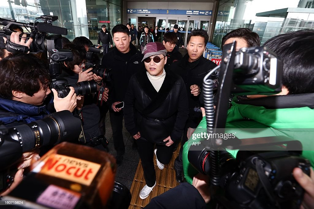 This picture taken on February 4, 2013 shows South Korean rapper Psy (C) arriving at the Incheon International Airport to take a one-day-rest after planes were delayed due to heavy snowfall. The rapper of 'Gangnam Style' is due to depart for Los Angeles on February 5. REPUBLIC OF KOREA OUT JAPAN OUT AFP PHOTO / STARNEWS