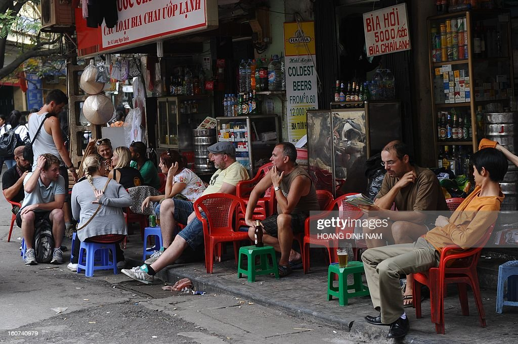 This picture taken on February 4, 2013 shows tourists drinking beer and coffee in the ancient quarter of Hanoi. According to the official statistics, some 6.8 million international tourists have visited the communist Southeast Asian nation in 2012. AFP PHOTO/HOANG DINH Nam