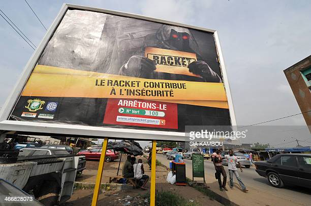 This picture taken on February 4 2014 shows a governmental advertisement reading 'Racket contributes to insecurity lets strop it' in a street of...