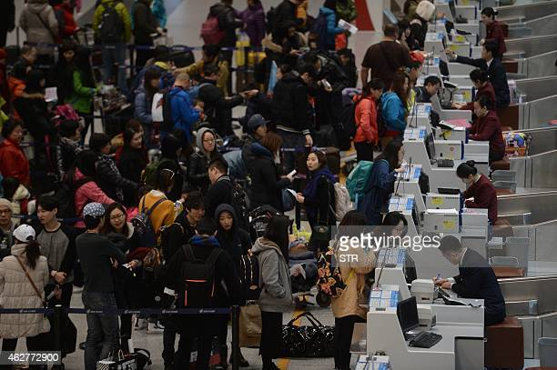 This picture taken on February 4 2015 shows passengers checking in at the service counters in Beijing Capital International Airport on the first day...