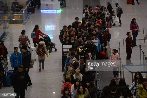 This picture taken on February 4 2015 shows passengers queuing up to check in at the service counters in Beijing Capital International Airport on the...