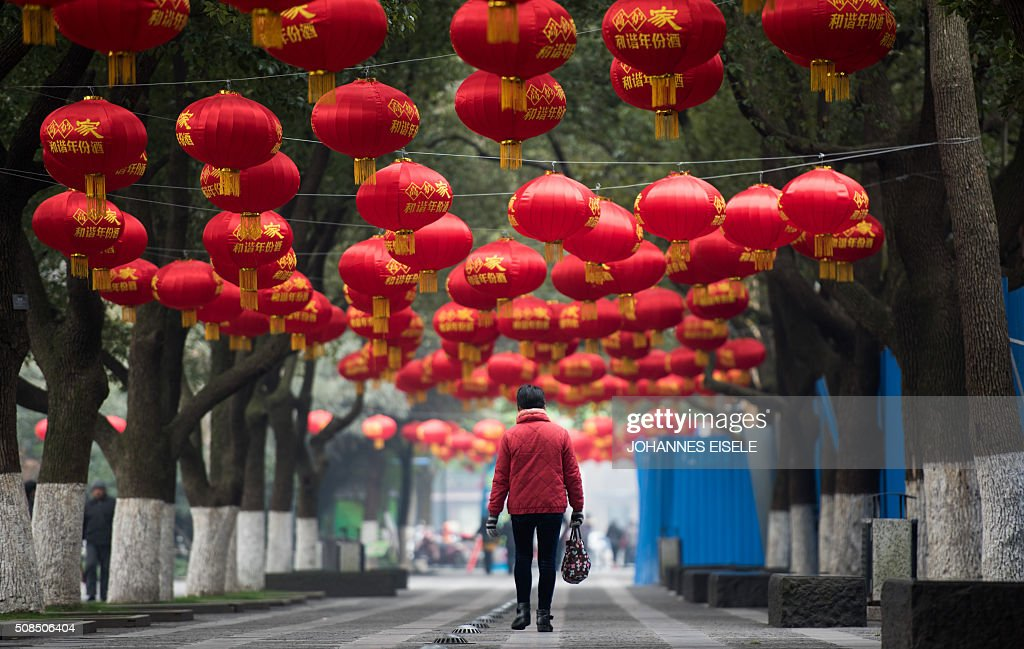 TOPSHOT - This picture taken on February 4, 2016 shows a woman walking in a park decorated with red lanterns ahead of the Lunar New Year in Changzhou. The Spring Festival, this year being the Year of the Monkey, China's most important holiday centering around family reunions, will fall on February 8.