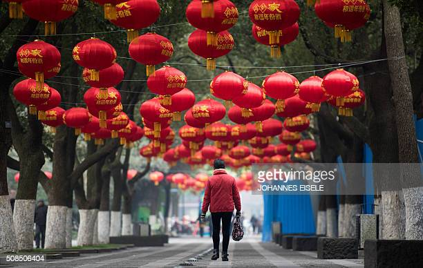 TOPSHOT This picture taken on February 4 2016 shows a woman walking in a park decorated with red lanterns ahead of the Lunar New Year in Changzhou...