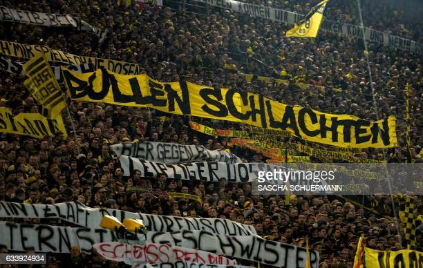 This picture taken on February 4 2017 shows supporters of Dortmund displaying banners prior to the German First division Bundesliga football match...