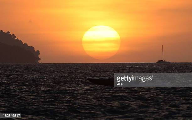 This picture taken on February 6 2013 shows a boat passing by during sunset in Kota Kinabalu Malaysia's Sabah state Kota Kinabalu formerly known as...