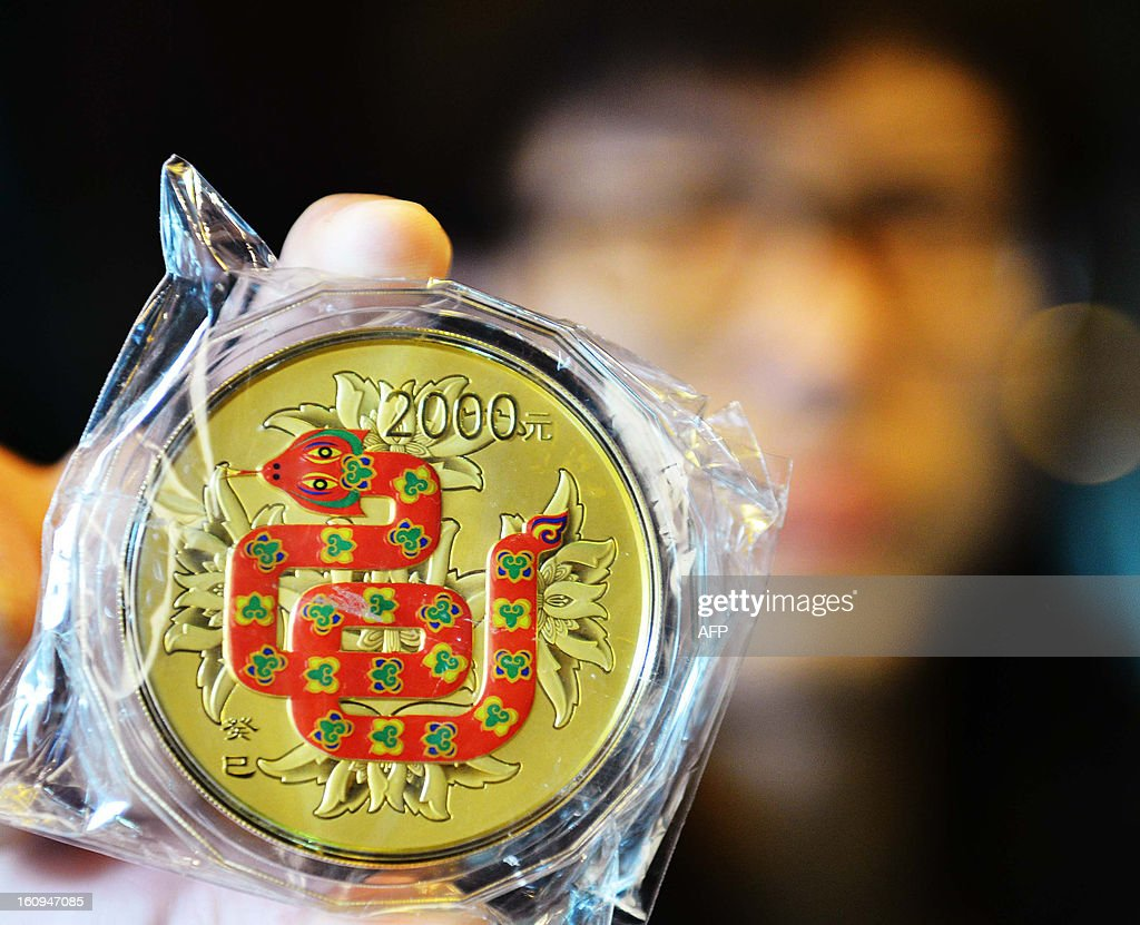 This picture taken on February 7, 2013 shows a salesman showing a gold coin with a snake image on it to mark the coming year of snake in a gold shop in Hangzhou, east China's Zhejiang province. All Chinese people arround the wolrd will welcome the Year of Snake that would come on February 10 this year until the Lantern festival. CHINA