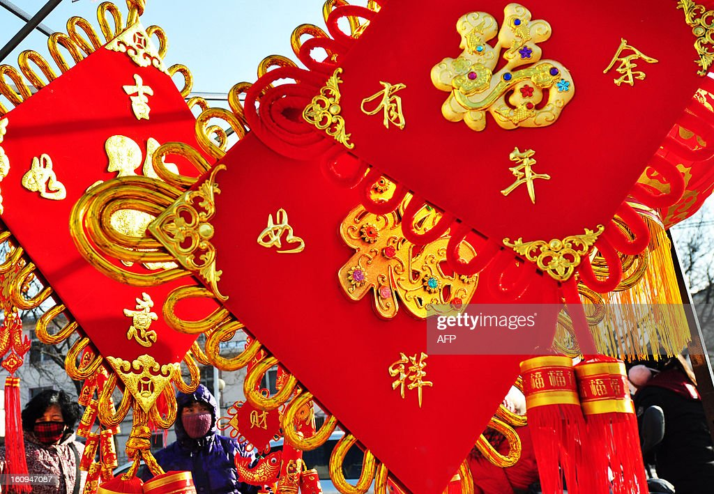 This picture taken on February 7, 2013 shows people buying lunar new year decorations with the word for luck, in Chinese 'Fu' in a market in Zouping, east China's Shandong province. The lunar new year, or spring festival, falls on February 10. CHINA OUT AFP PHOTO
